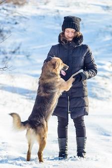 Menina com cachorro caminhando no inverno