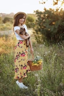 Menina com cachorro e cesta de piquenique na caminhada ao pôr do sol de verão