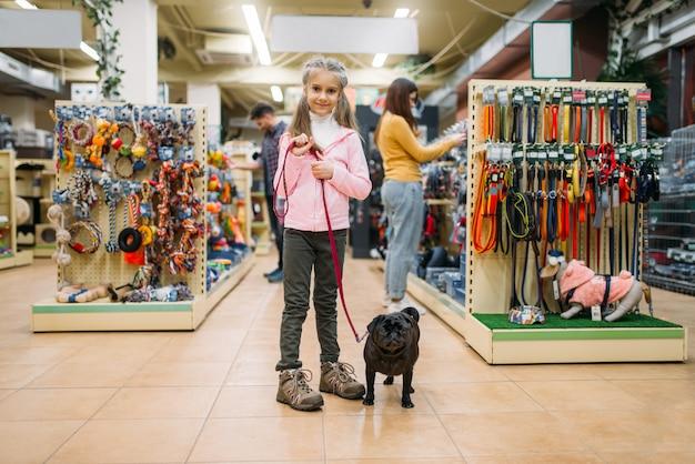 Menina com cachorro em pet shop, amizade