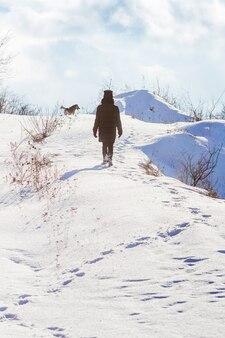 Menina com cachorro enquanto caminhava na natureza no inverno