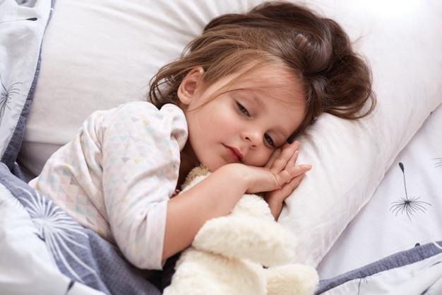 Menina com cachorro macio branco relaxante na cama, abraçando seu brinquedo, mantém os olhos abertos, deitado no travesseiro sob o cobertor quente, encantadora criança do sexo feminino com cabelos escuros, vestindo pijama branco.