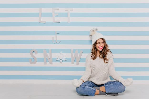 Menina com cachos meditando no chão e desviando o olhar com um sorriso. retrato de corpo inteiro em parede listrada de branco e azul