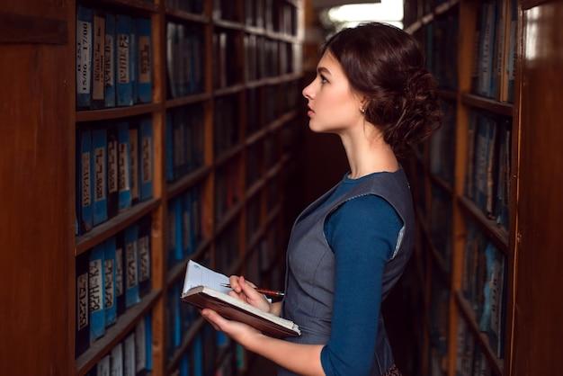 Menina com caderno selecione o livro didático na biblioteca.