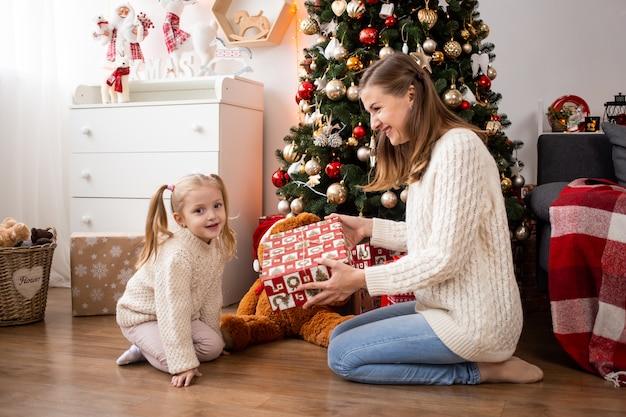Menina com caixa de presente e sua mãe em casa perto de árvore de natal