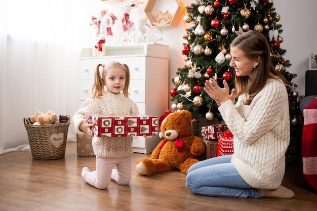 Menina com caixa de presente em casa perto de árvore de natal