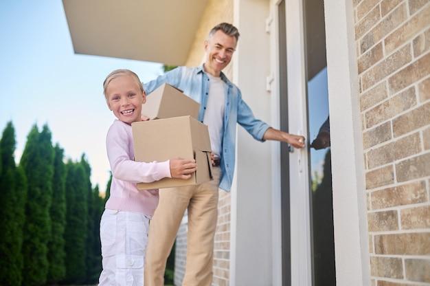 Menina com caixa e pai entrando em casa