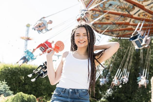 Menina com caixa trança penteado no parque