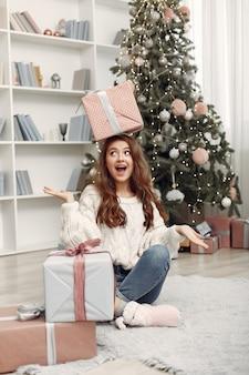 Menina com caixas de natal. mulher em casa. ladu se preparando para as férias.