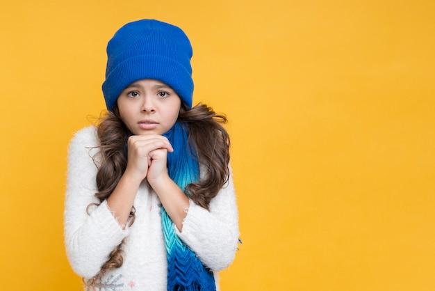 Menina com calafrios, mesmo em roupas de inverno