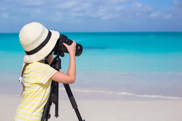 Menina com câmera em um tripé na praia de areia branca