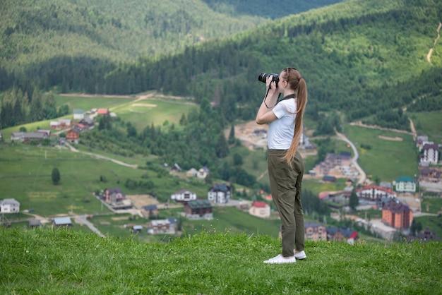Menina com câmera fica em uma colina e fotografar a natureza. floresta no fundo