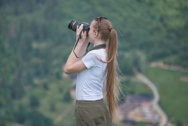 Menina com câmera fica uma colina e fotografar a natureza. forest on