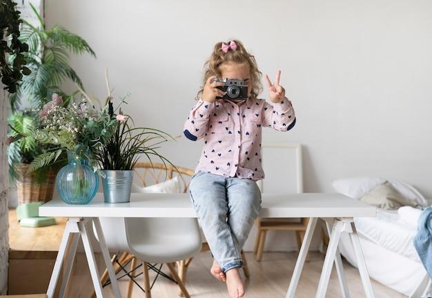 Menina, com, câmera, mostrando, símbolo paz
