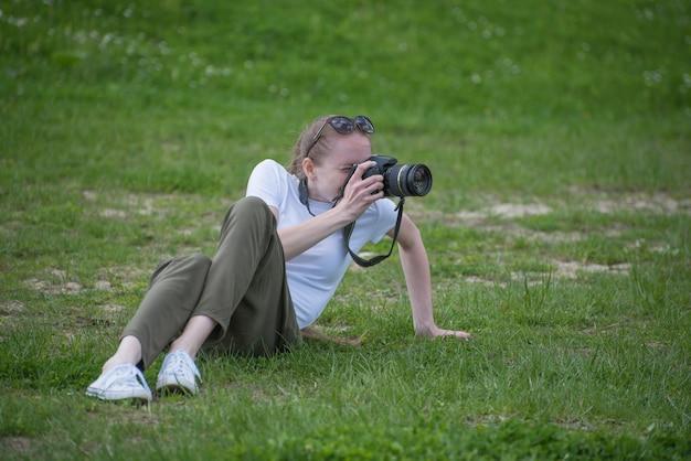Menina com câmera senta-se em uma colina e fotografia natureza. dia de verão