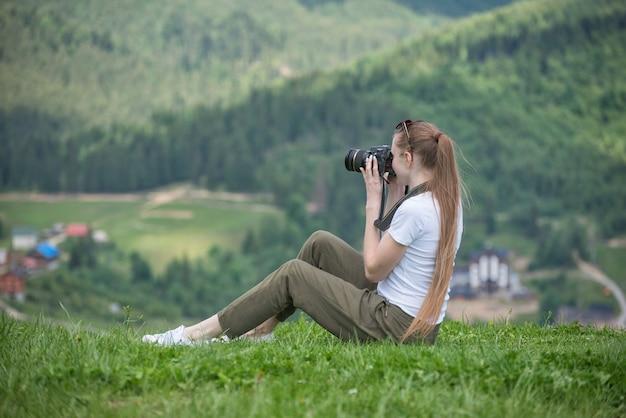 Menina com câmera senta-se em uma colina e montanhas fotografias. dia de verão