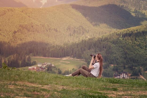 Menina com câmera senta-se em uma colina e montanhas fotografias.