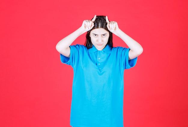 Menina com camisa azul em pé na parede vermelha e mostrando orelhas de lobo.