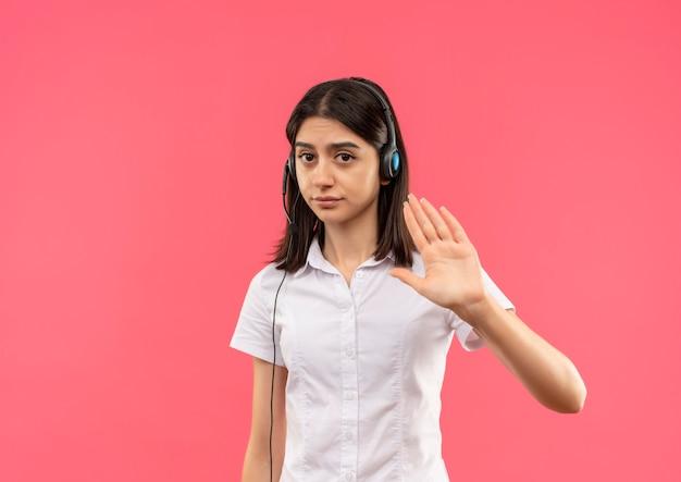Menina com camisa branca e fones de ouvido, fazendo um gesto de parada com a mão, dizendo para não se aproximar em pé sobre a parede rosa