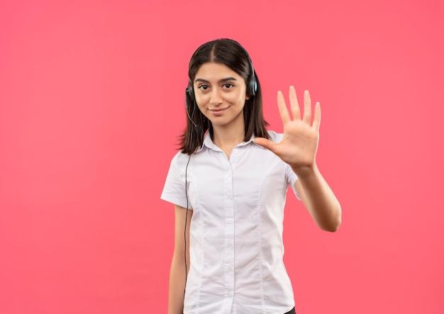 Menina com camisa branca e fones de ouvido, mostrando e apontando com os dedos para o número cinco, sorrindo em pé sobre a parede rosa