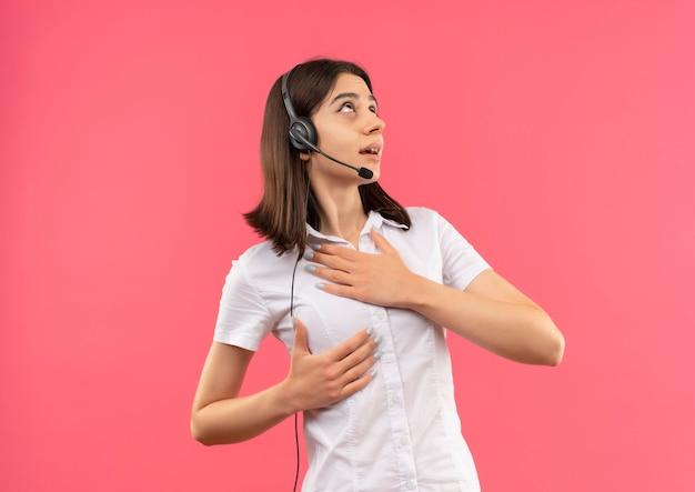 Menina com camisa branca e fones de ouvido, olhando para o lado com a mão no peito preocupada em pé sobre a parede rosa