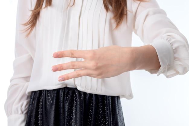 Menina com camisa branca estendida a mão e três dedos aparecendo na lateral