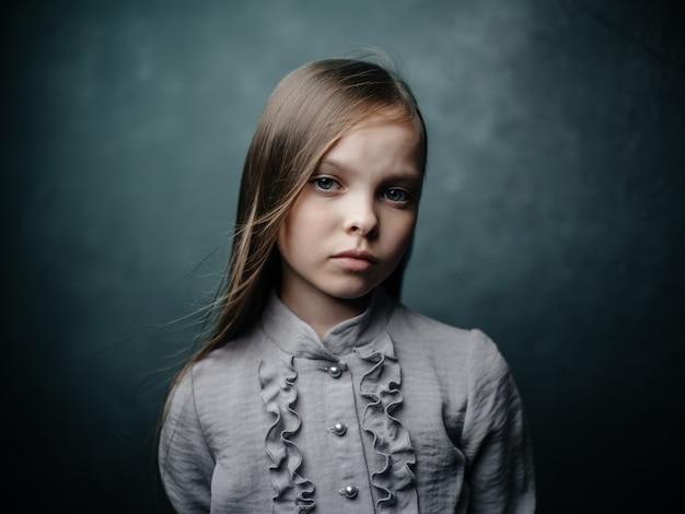 Menina com camisa cinza posando emoções de estúdio closeup