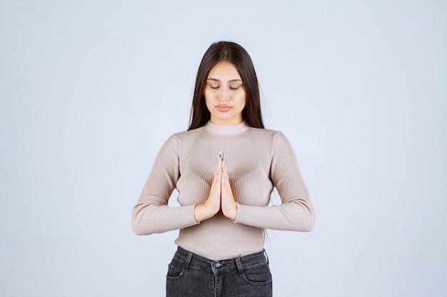 Menina com camisa cinza, unindo as mãos e orando.
