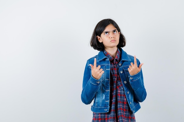 Menina com camisa, jaqueta apontando para cima e parecendo indecisa, vista frontal.