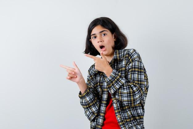 Menina com camisa, jaqueta apontando para o lado e parecendo surpresa, vista frontal.