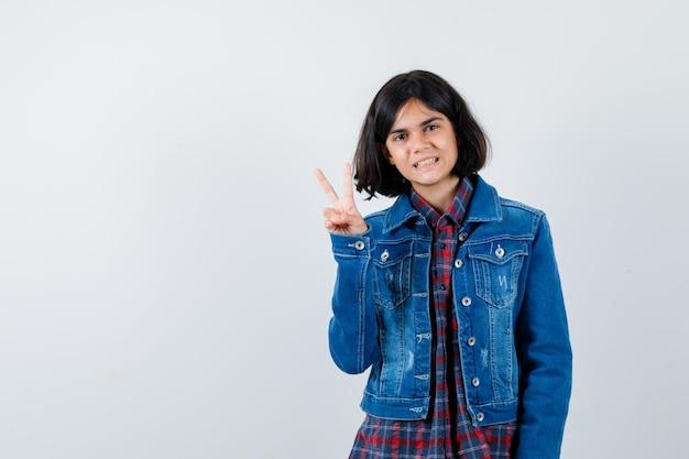 Menina com camisa, jaqueta mostrando o sinal de v e parecendo confiante, vista frontal.