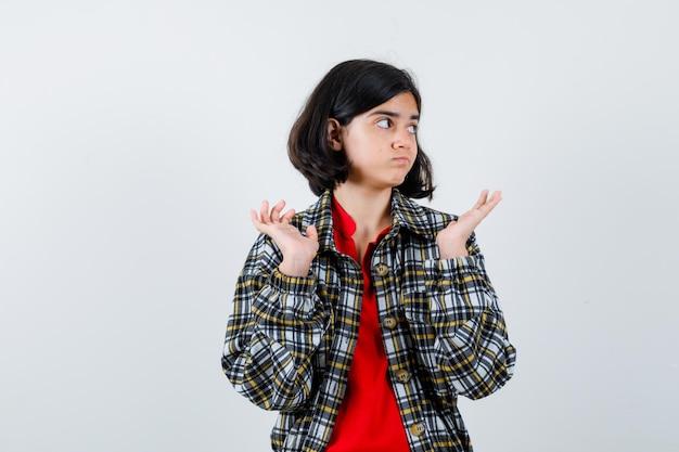 Menina com camisa, jaqueta, mostrando um gesto de impotência, vista frontal.