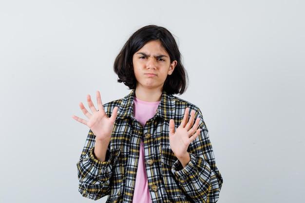 Menina com camisa, jaqueta, mostrando um gesto de rejeição e parecendo relutante, vista frontal.