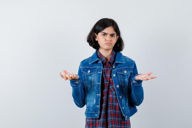 Menina com camisa, jaqueta, mostrando um gesto desamparado e parecendo sombria, vista frontal.