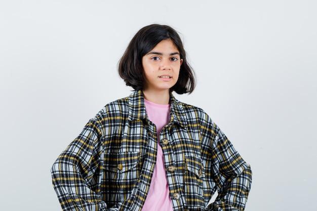 Menina com camisa, jaqueta, olhando para a câmera e olhando focada, vista frontal.