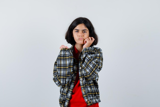 Menina com camisa, jaqueta, segurando a mão no rosto e parecendo chateada, vista frontal.