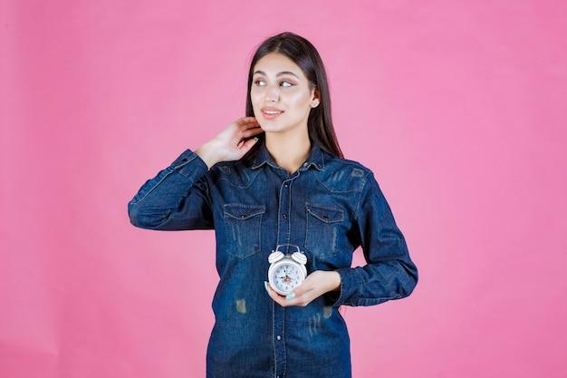 Menina com camisa jeans segurando e promovendo um despertador
