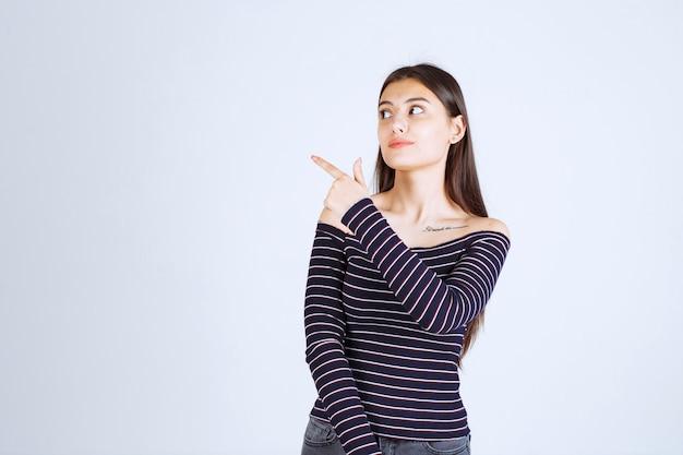 Menina com camisa listrada, apontando para cima e mostrando emoções.