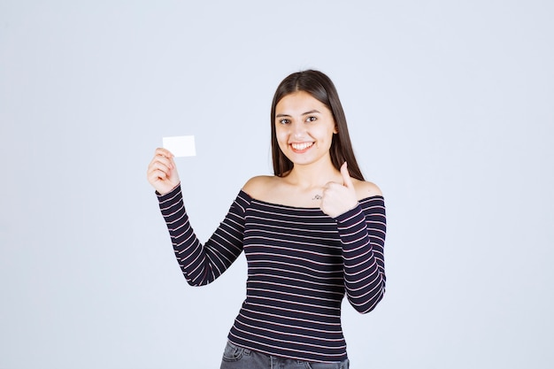 Menina com camisa listrada, apresentando seu cartão de visita com confiança.