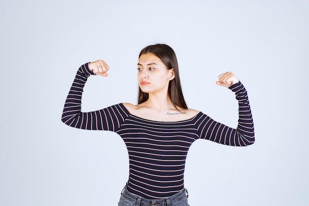 Menina com camisa listrada, demonstrando os músculos do braço.