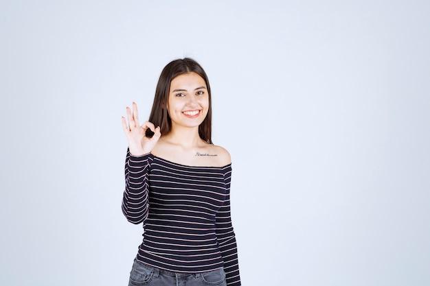 Menina com camisa listrada, fazendo sinal de gozo.