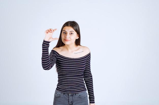 Menina com camisa listrada, mostrando a medida ou quantidade estimada de um produto.