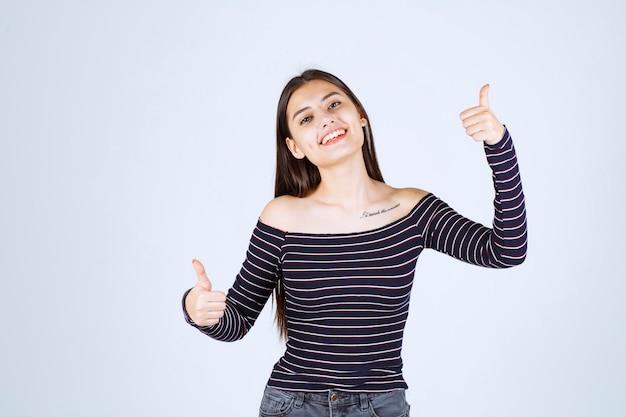Menina com camisa listrada, mostrando sinal de bom prazer.