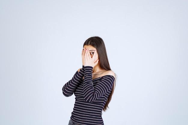 Menina com camisa listrada, olhando por entre os dedos.