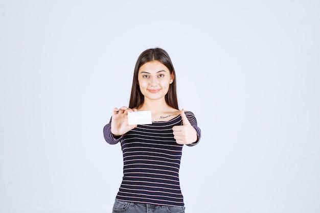 Menina com camisa listrada segura um cartão de visita e mostrando o polegar para cima o sinal.
