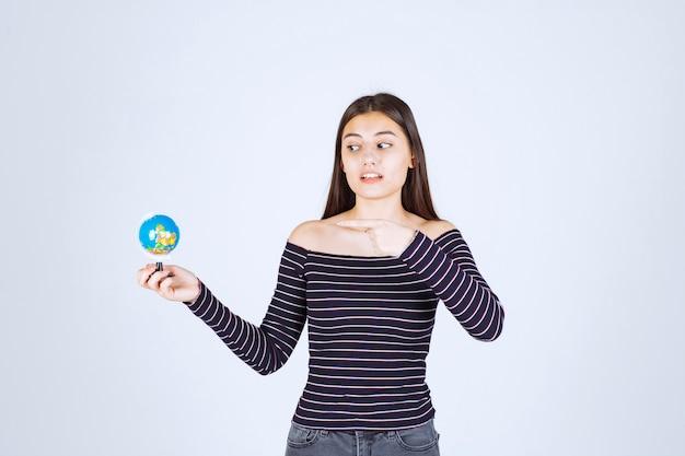 Menina com camisa listrada segurando um mini globo e apontando para ele.