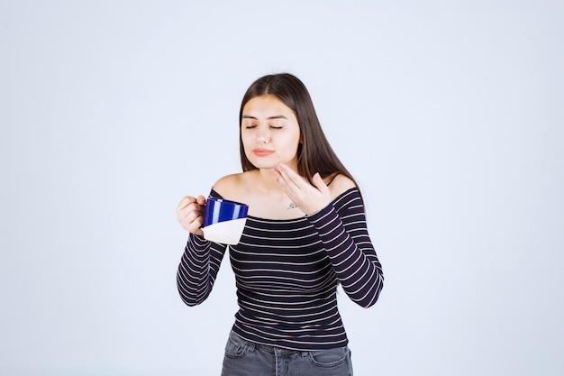 Menina com camisa listrada, segurando uma caneca de café e cheirando-a.