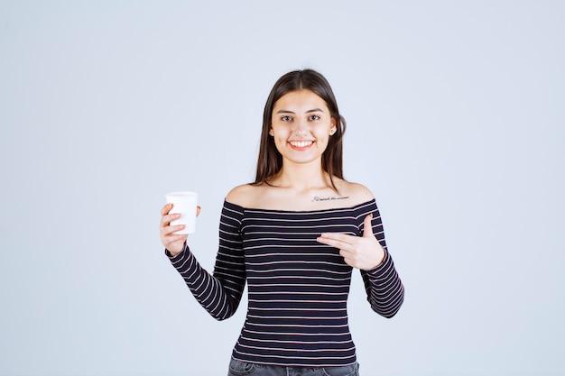 Menina com camisa listrada segurando uma xícara de café de plástico e apresentando-a como um produto.