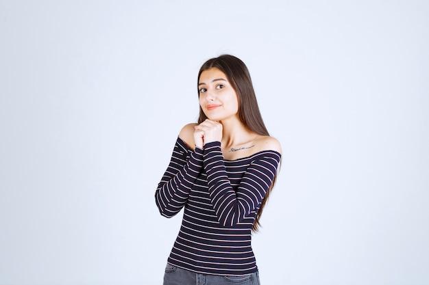 Menina com camisa listrada, unindo as mãos e orando.