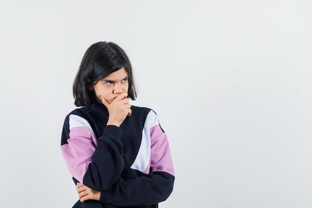 Menina com camisa, segurando a mão no queixo e olhando pensativa, vista frontal.