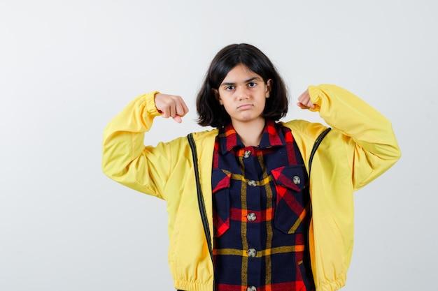 Menina com camisa xadrez, jaqueta mostrando o gesto do vencedor e parecendo com sorte, vista frontal.